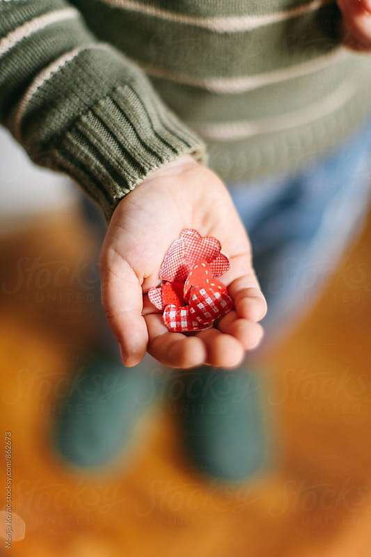 Child's hand holding red hearts  by Marija Kovac for Stocksy United