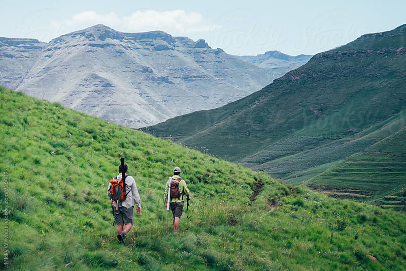 hikers on a mountain track  by Micky Wiswedel for Stocksy United