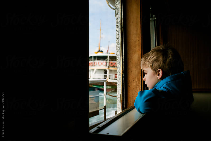 A boy looks out of the window of an Istanbul ferryboat. A similar boat can be see through the window. by Julia Forsman for Stocksy United