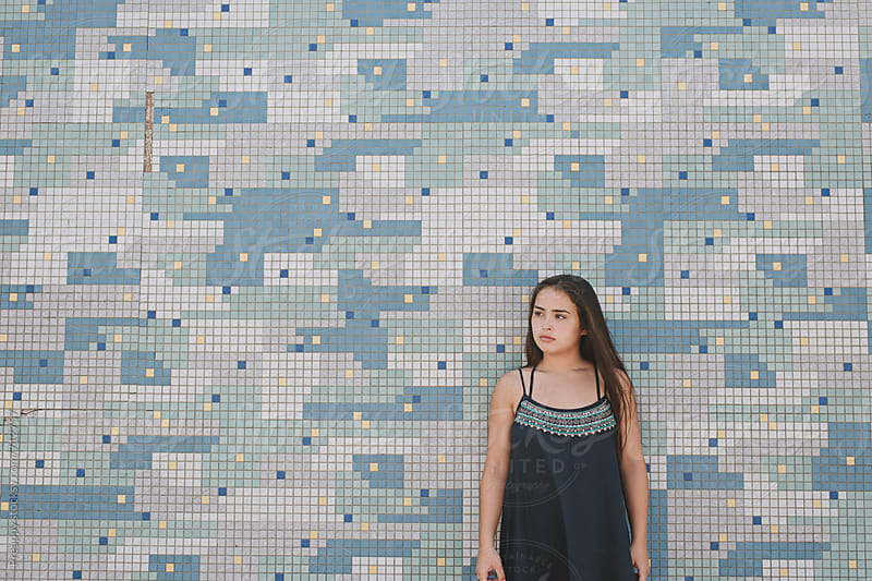 Teenage girl standing against tiled wall by Preappy for Stocksy United