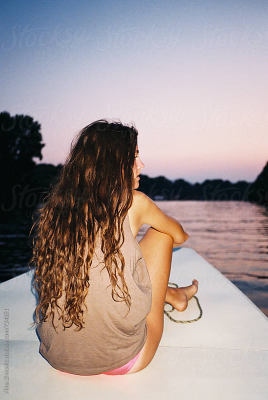 A young woman sitting on the prow of the boat.  by Nina Zivkovic for Stocksy United