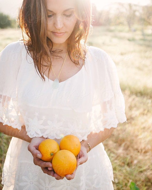 Pretty lady holding oranges in a field  by Kristin Rogers Photography for Stocksy United
