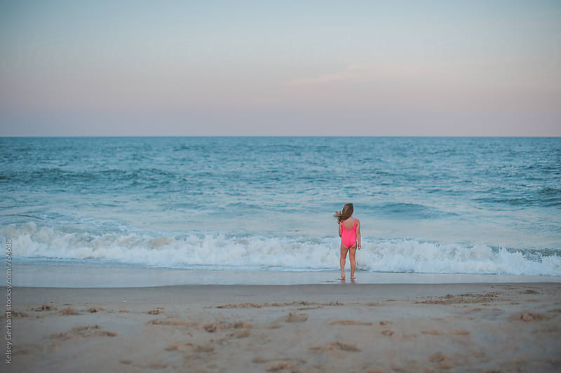 Small girl in a pink swimsuit faces the ocean at sunset. by Kelsey Gerhard for Stocksy United