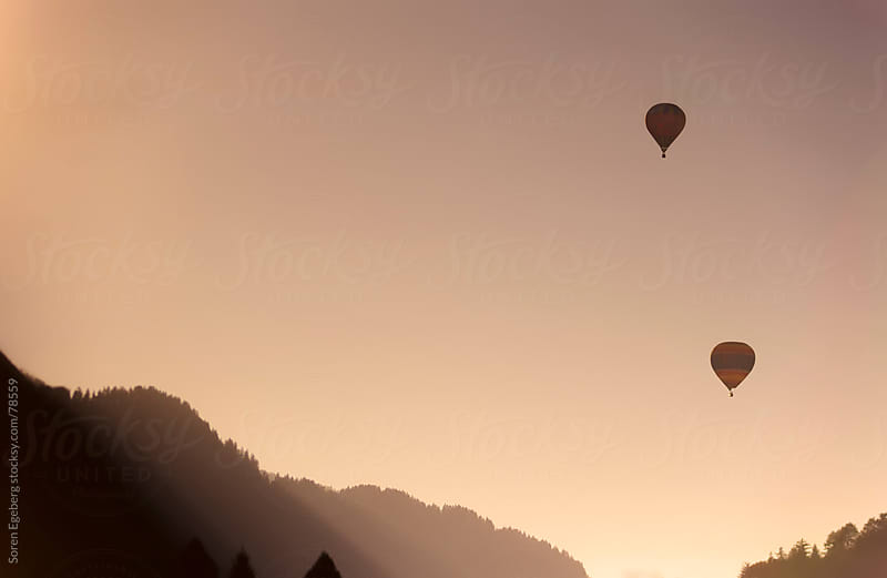 Hot air balloon flying in the mountains by Soren Egeberg for Stocksy United