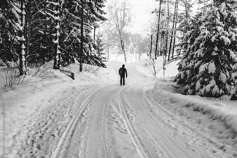 Man Walking Down Winter Road by Stephen Morris for Stocksy United