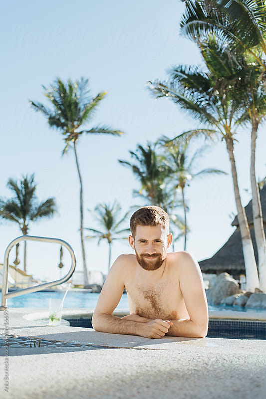 Happy untanned man on holidays in a hot tub surrounded by palm trees by Ania Boniecka for Stocksy United