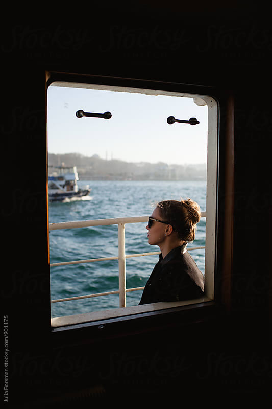 A woman framed by a ferryboat window looks out towards historical Istanbul. by Julia Forsman for Stocksy United