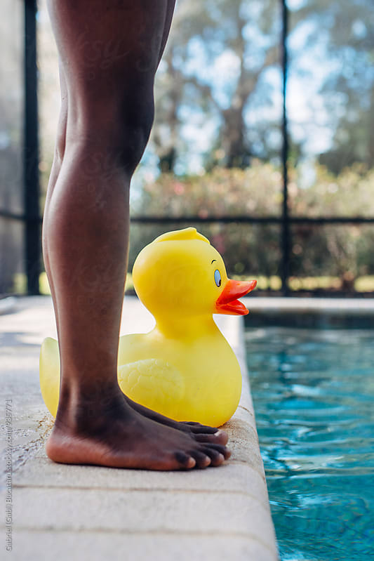 Black girl's legs next to her rubber duck by a swimming pool by Gabriel (Gabi) Bucataru for Stocksy United
