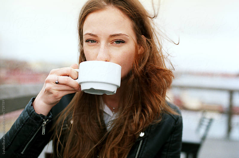 Portrait of young redhead woman drinking coffee outdoors by Lyuba Burakova for Stocksy United