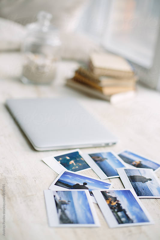 Laptop and instant photos on desk by Andrey Pavlov for Stocksy United