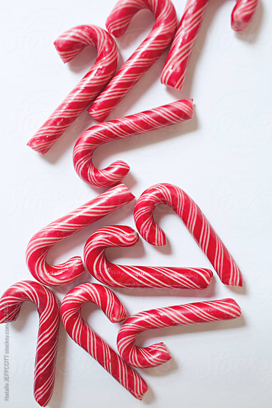 Red and whited striped Christmas candy canes on a white background by Natalie JEFFCOTT for Stocksy United