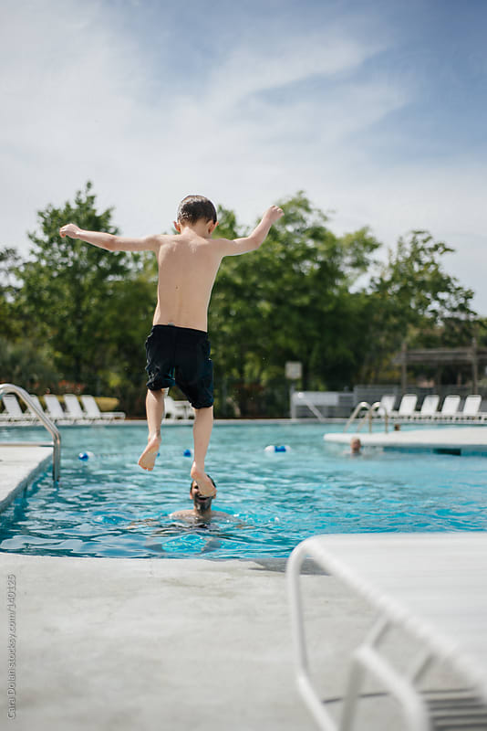 Boy leaps into a swimming pool while on vacation with his family by Cara Dolan for Stocksy United