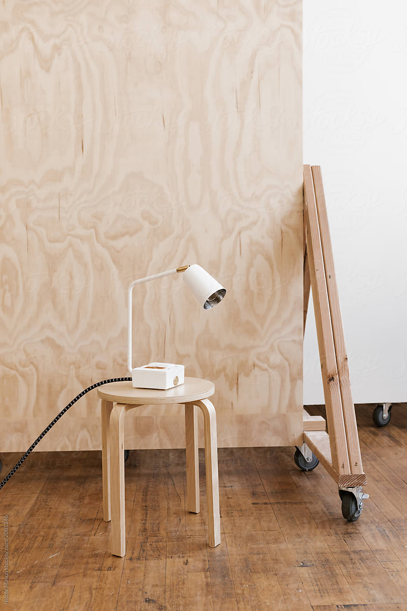 Modern White Desk Lamp On Stool In Front Of Plywood Backdrop Por Nicole Mason Stocksy United
