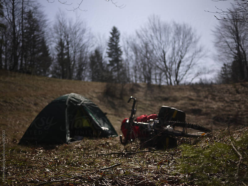 Bicycle lying by the tent at night by forest by Martin Matej for Stocksy United