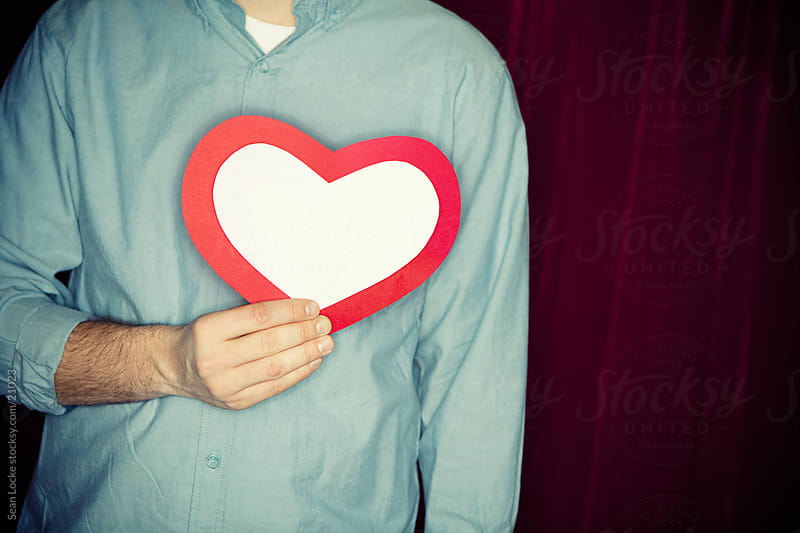 Valentine: Man Holds Paper Heart Over Real Heart by Sean Locke for Stocksy United