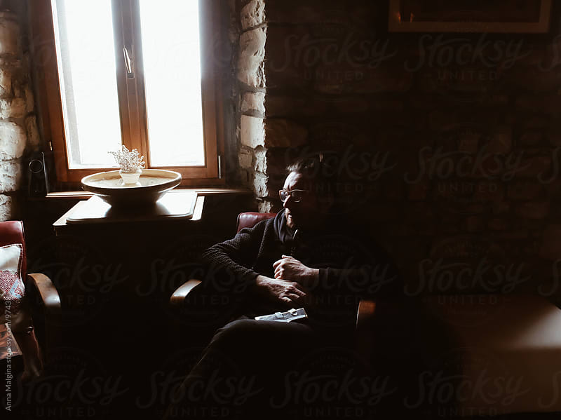 A man sitting in old living room by Anna Malgina for Stocksy United