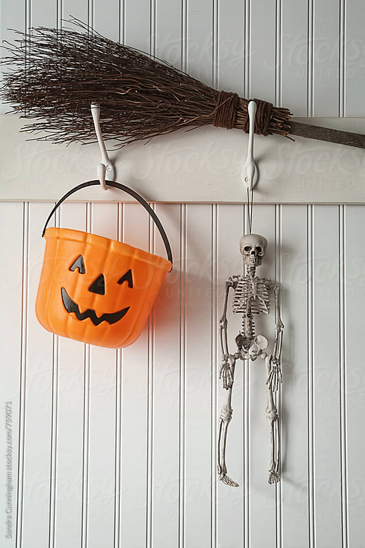 Toy skeleton and candy bucket hanging on coat hook by Sandra Cunningham for Stocksy United