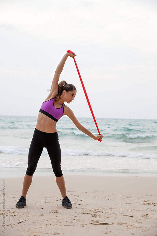 Woman exercising at the beach with rubber band by Jovo Jovanovic for Stocksy United