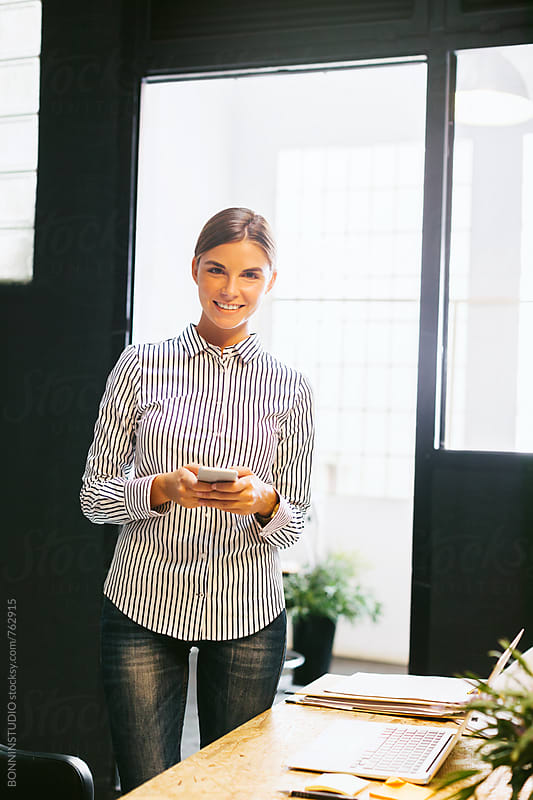 Young businesswoman using phone standing in a modern office. by BONNINSTUDIO for Stocksy United