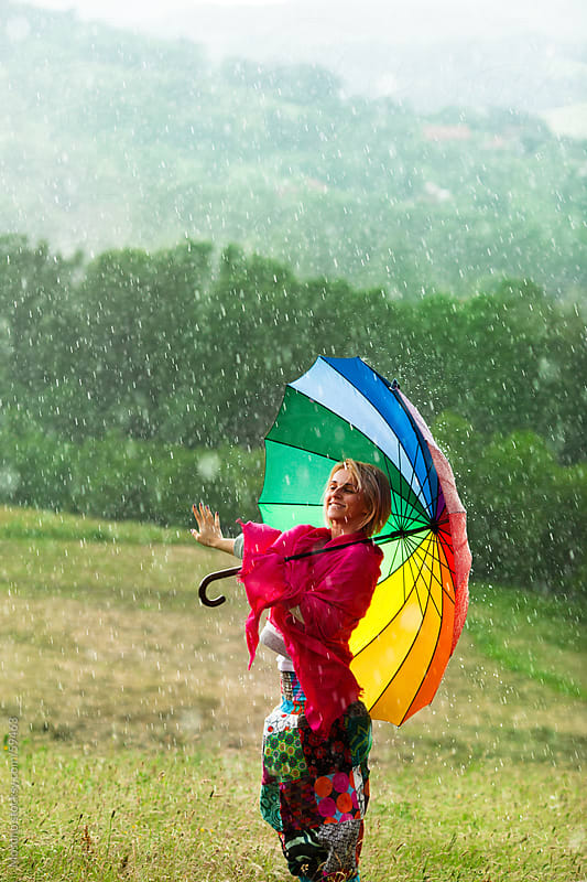Woman with colorful umbrella enjoying rain in the meadow. by Mosuno for Stocksy United