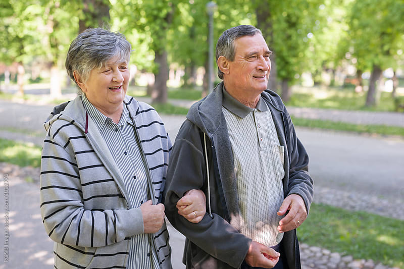 Portrait of an active senior couple walking in the park by RG&B Images for Stocksy United