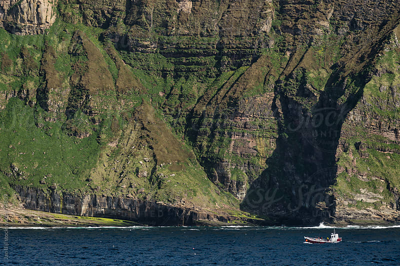 fishermen boat under the cliffs of hoy island, orkney, scotland by Jan Bijl for Stocksy United