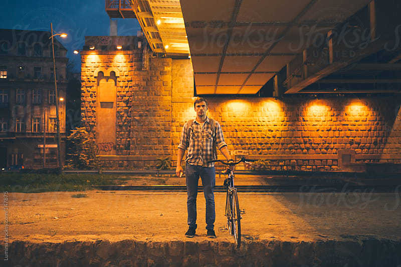 Man With a Bike at Night by Lumina for Stocksy United