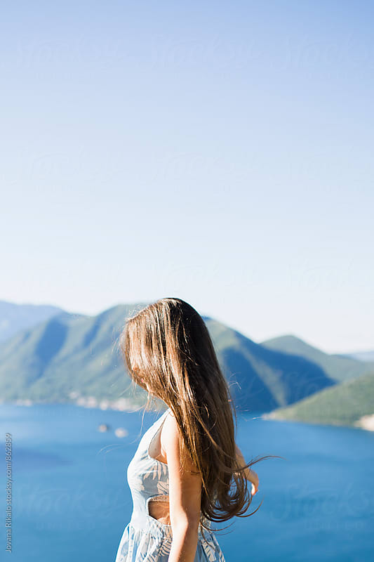 Young woman standing on the hill by the peaceful sea at sunrise by Jovana Rikalo for Stocksy United