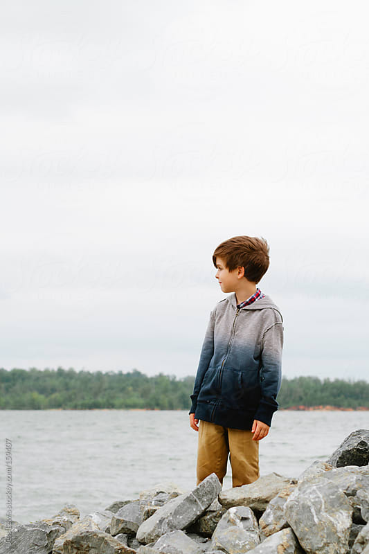 young boy looking at lake by Jess Lewis for Stocksy United
