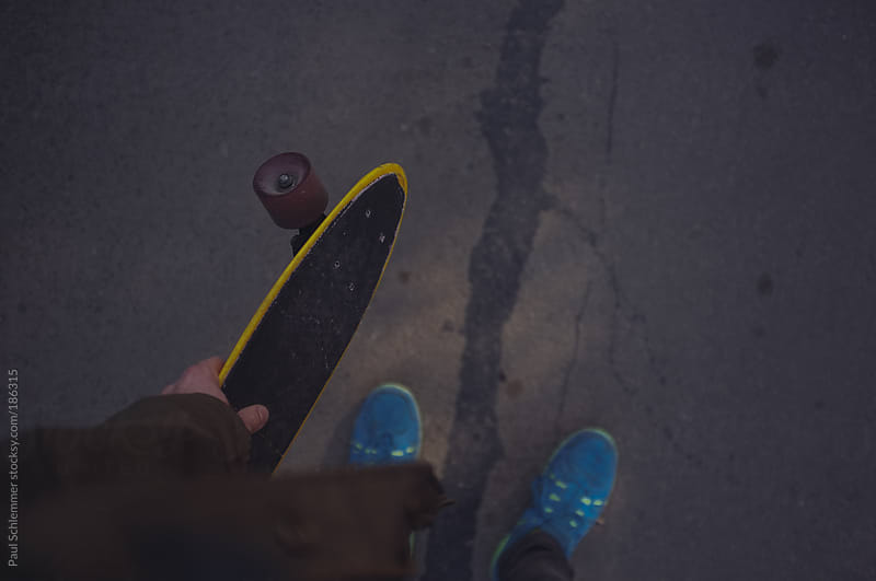 holding a plastic penny skateboard by Paul Schlemmer for Stocksy United