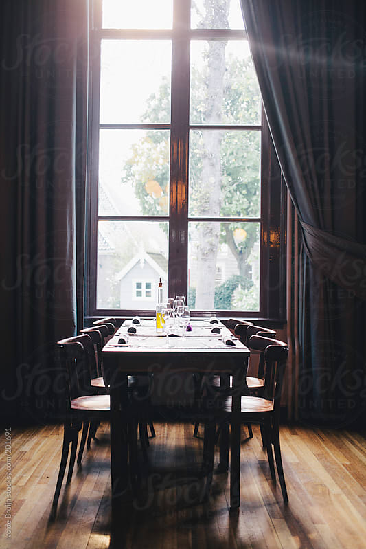 Empty dinner table with a big window at the end with light falling in by Ivo de Bruijn for Stocksy United