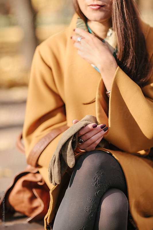 Young woman in yellow coat sitting on bench in park. by Ilya for Stocksy United