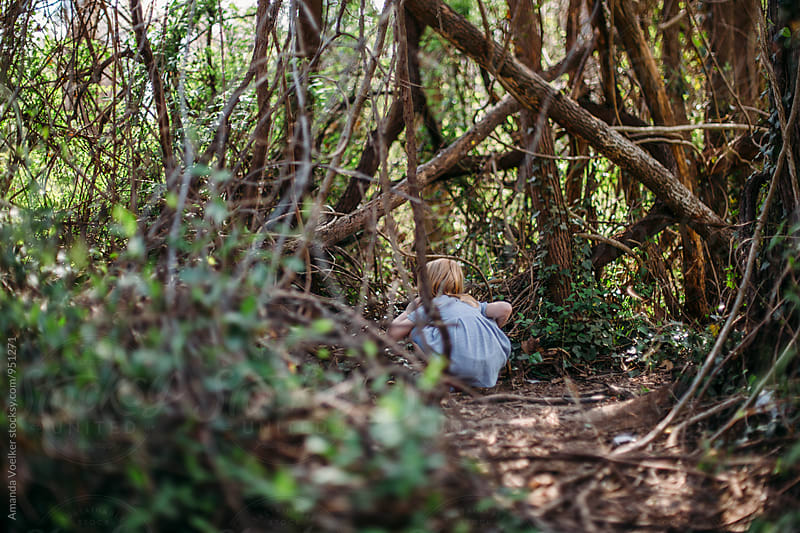 A little Girl peeks into the branches in the woods by Amanda Voelker for Stocksy United