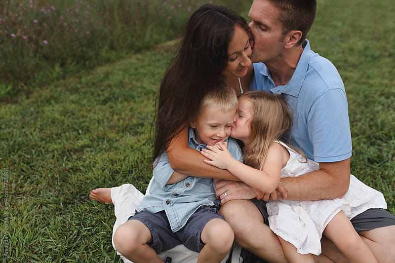 A young family hugs outdoors, sister kisses brother by Amanda Worrall for Stocksy United