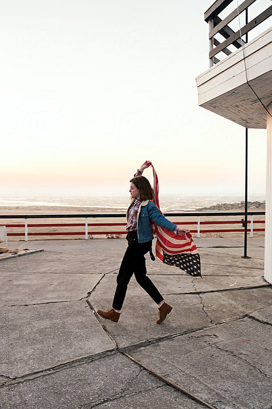 Young brunette running with waving American flag by T-REX & Flower for Stocksy United