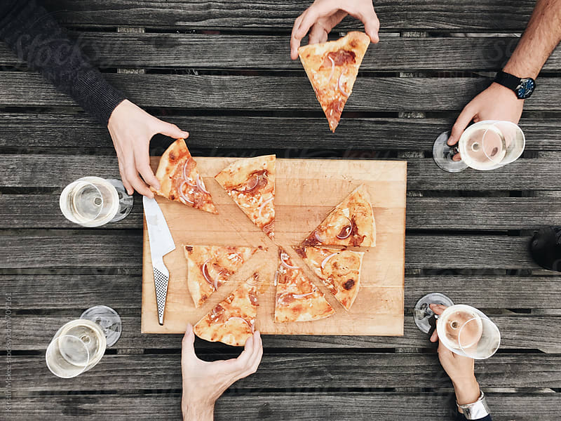 Four friends enjoy pizza outdoors by Kirstin Mckee for Stocksy United