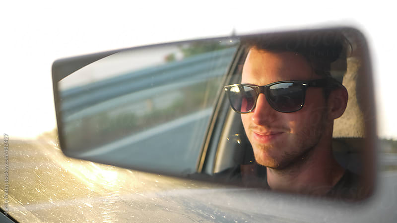 Young driver smiling in the car mirror by Martin Matej for Stocksy United