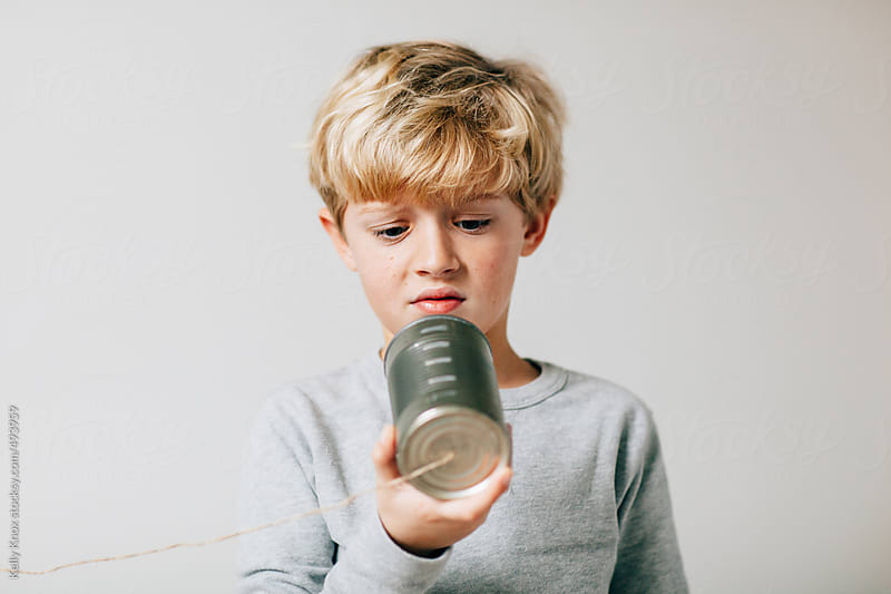 dissatisfied boy looking at his lame tin can phone by Kelly Knox for Stocksy United