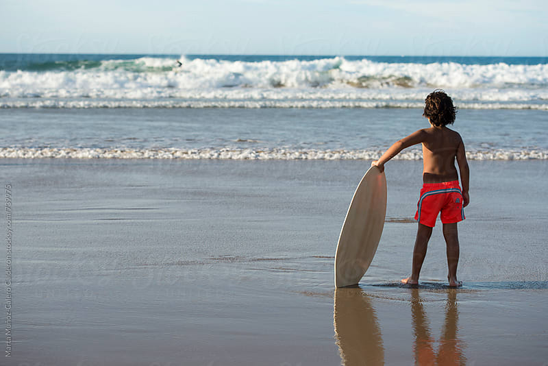 Boy holding a Surf slide board looking the ocean by Marta Muñoz-Calero Calderon for Stocksy United