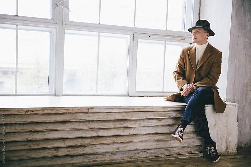 Stylish man sitting on a windowsill by Andrey Pavlov for Stocksy United