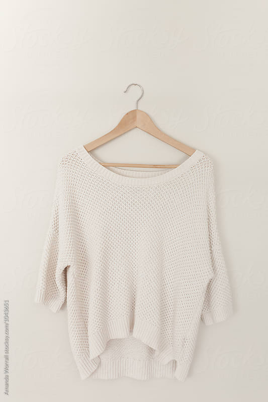 A minimalist image of an off white sweater hanging on a wood hanger by Amanda Worrall for Stocksy United