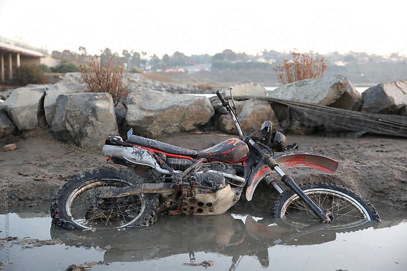 Motorcycle Laying In A mud Puddle by Carey Haider for Stocksy United