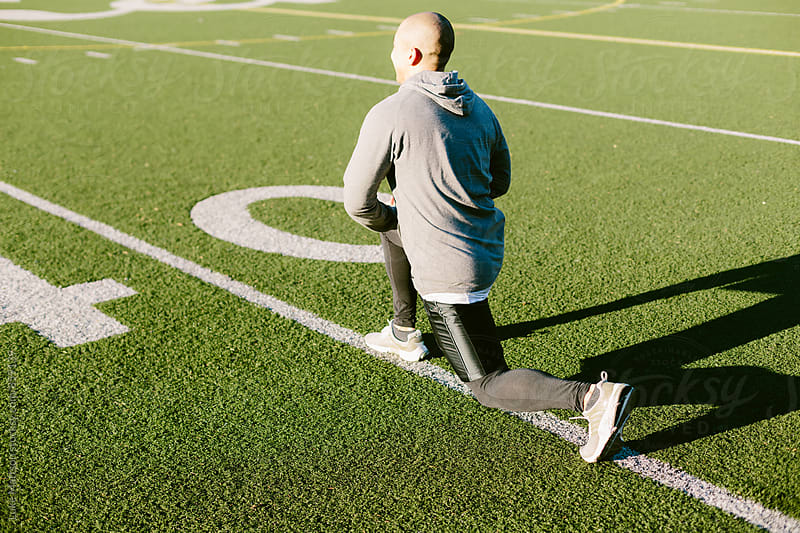 Athletic Man Doing Leg Lunges During Workout Routine On Turf Field by Luke Mattson for Stocksy United