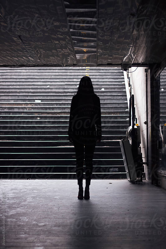Girl standing in an empty metro by Jovana Rikalo for Stocksy United