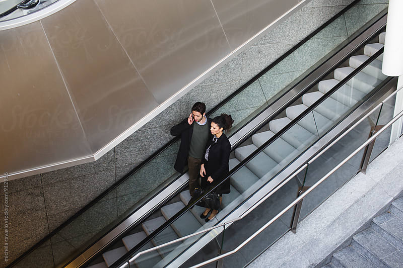 Business woman and man on escalators by michela ravasio for Stocksy United