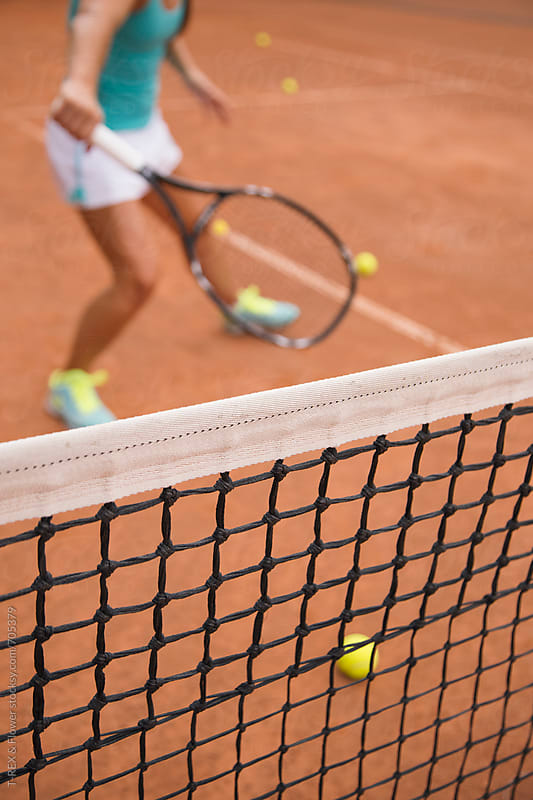 Closeup of the tennis net and silhouette of the player by Danil Nevsky for Stocksy United