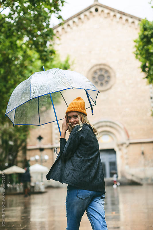 Smiling blonde woman walking with an umbrella in a rainy day. by BONNINSTUDIO for Stocksy United