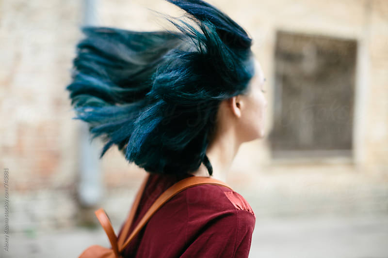 young woman with blue hair running by Alexey Kuzma for Stocksy United