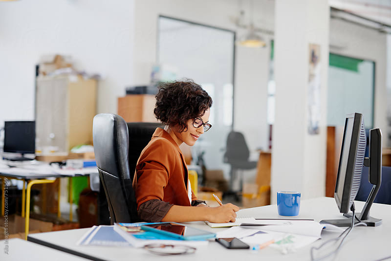 Business woman working on a creative project in a startup office by Aila Images for Stocksy United