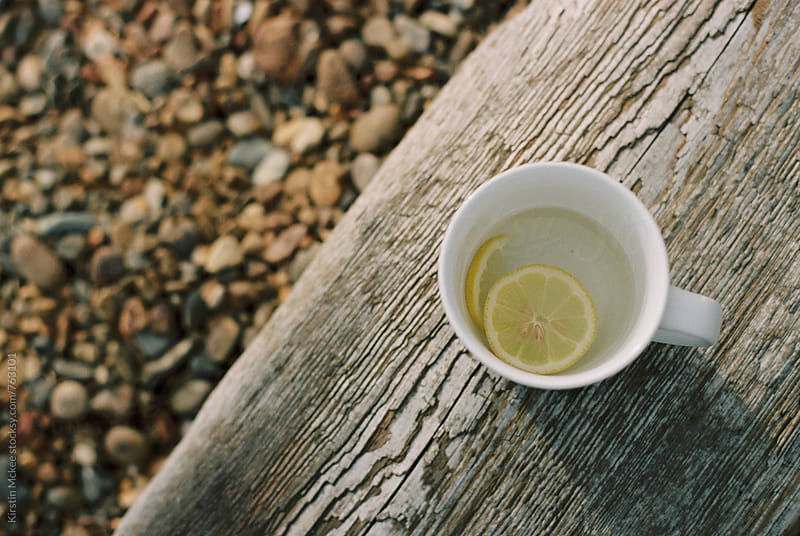 Cup of lemon tea on the beach by Kirstin Mckee for Stocksy United